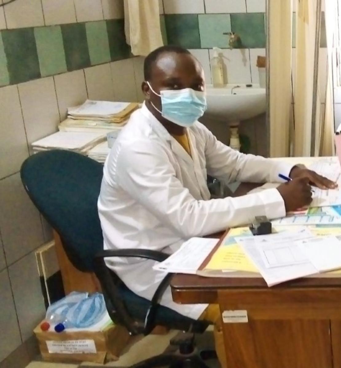 穿着白大卦的医生(左)为坐在桌子另一边的患者看诊。