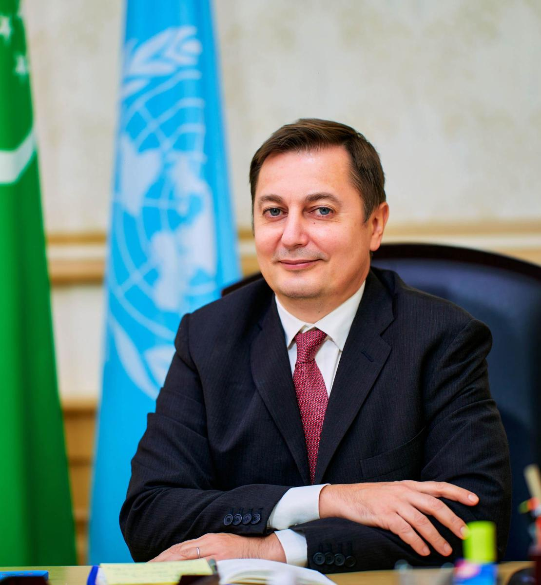 Un hombre con traje sonríe a la cámara con las banderas de Turkmenistán y de las Naciones Unidas.