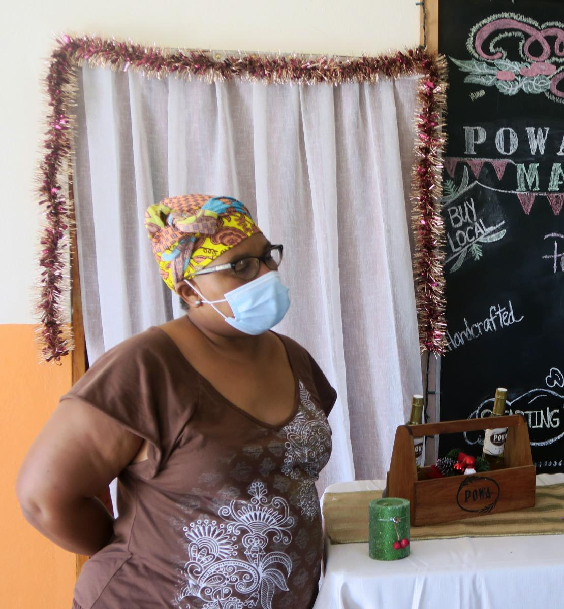 A woman wearing a face mask stands in front of her homemade oils and soaps at a POWA-sponsored market.