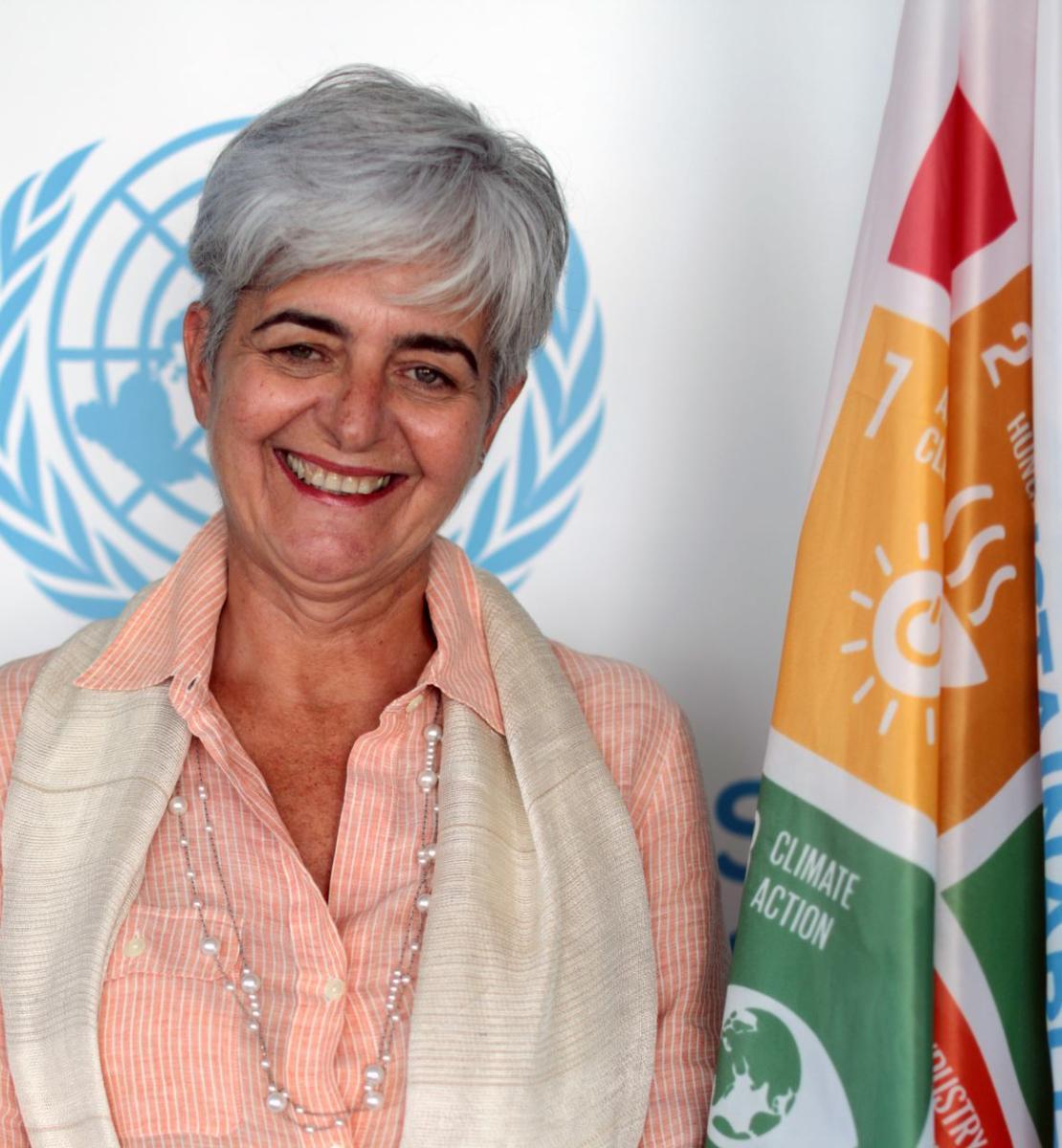 一名女性在联合国可持续发展目标旗帜和联合国标志前对镜头微笑。