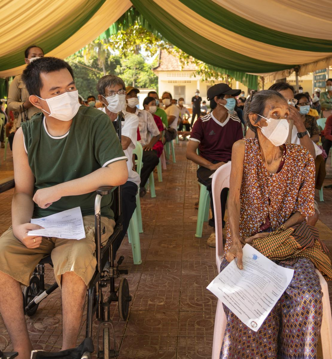 Elder and people with disabilities sit socially distanced and masked as they wait for their vaccinations.