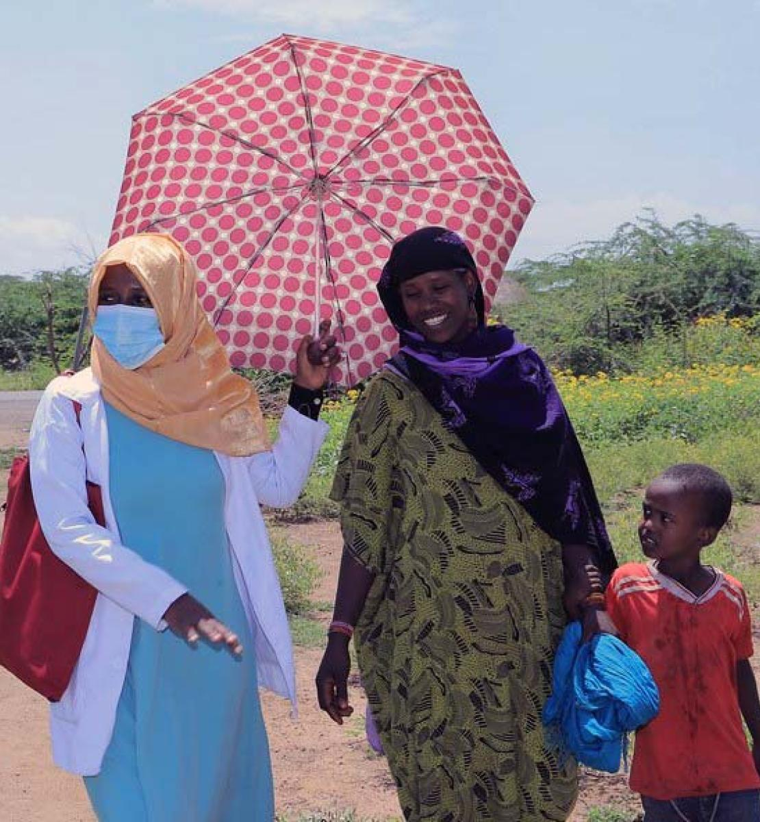 One woman wearing a face masks holds an umbrella as she walks side-by-side with a woman and her child.