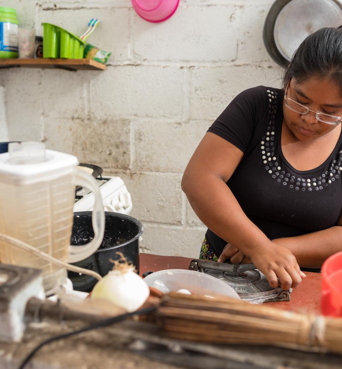 Une femme vêtue d'un haut noir prépare un repas dans une cuisine.