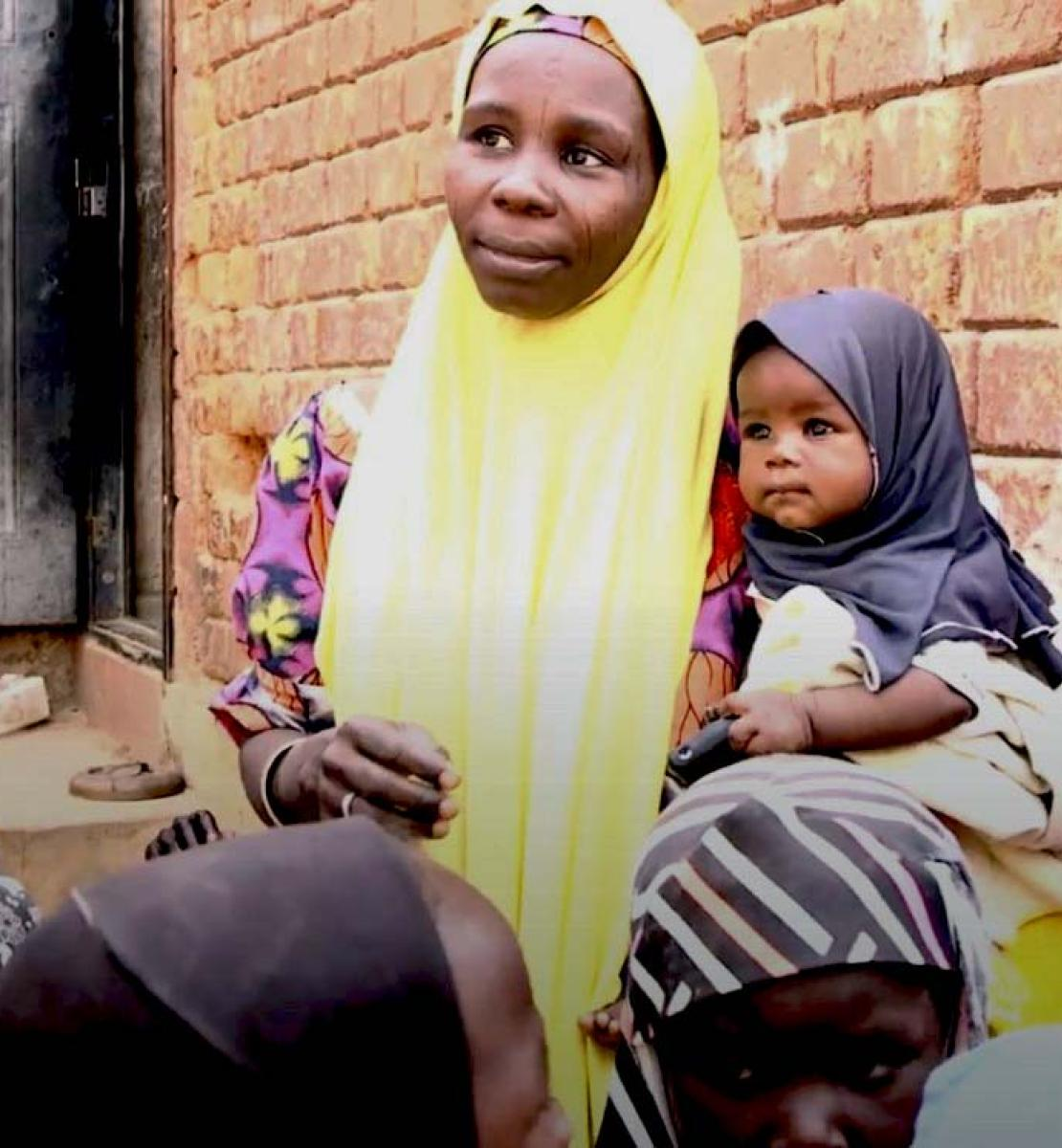 A woman in a yellow hijab holds a baby in her arms as she speaks to other women.