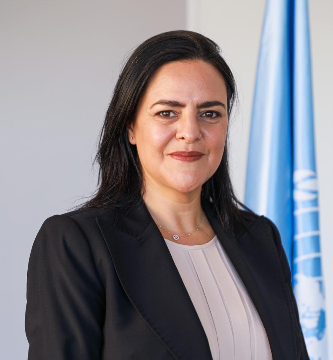 一位身穿黑色西装外套的妇女直视镜头,身后是联合国旗。