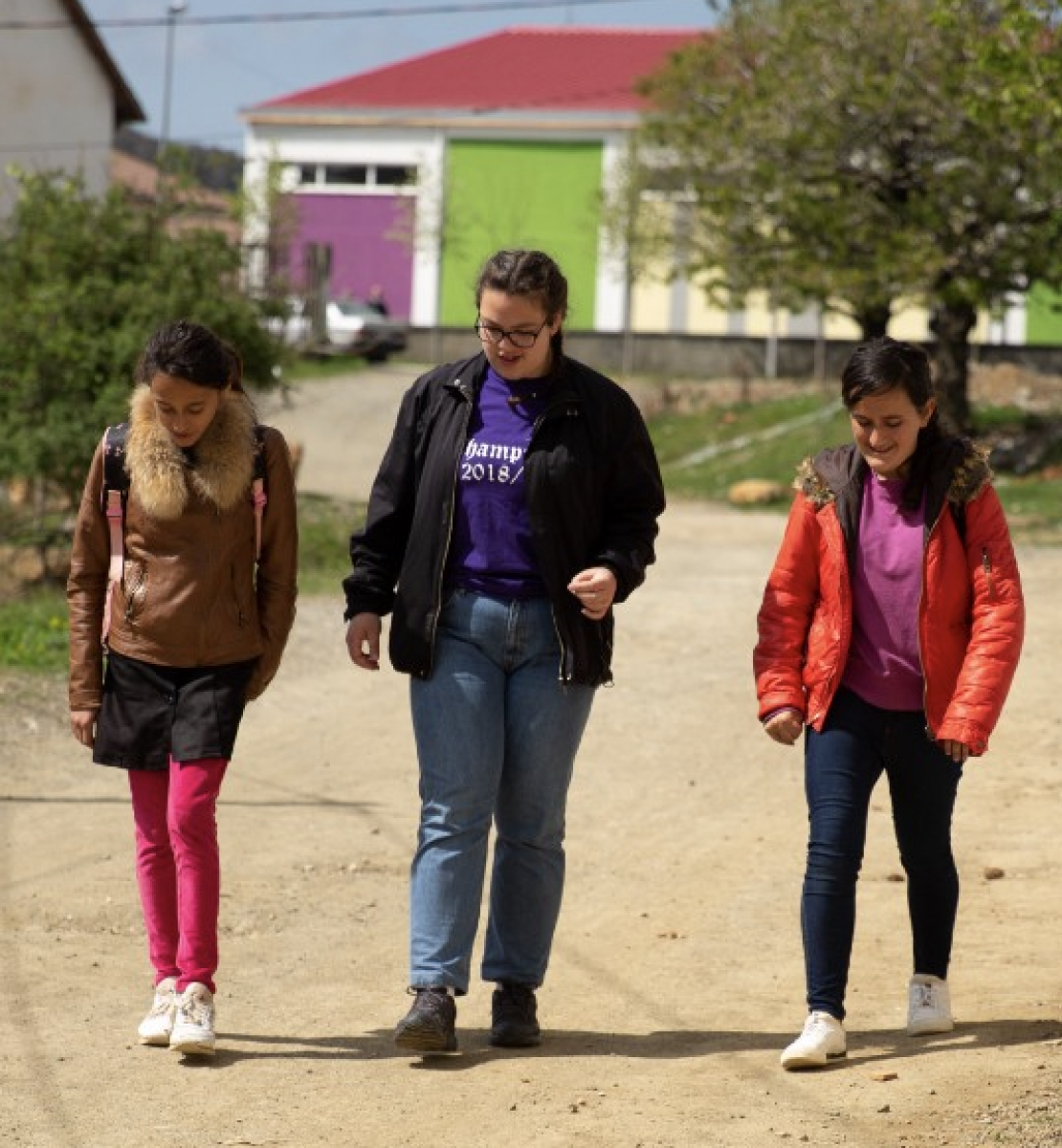 Three young girls walk down a dirt road in jackets.