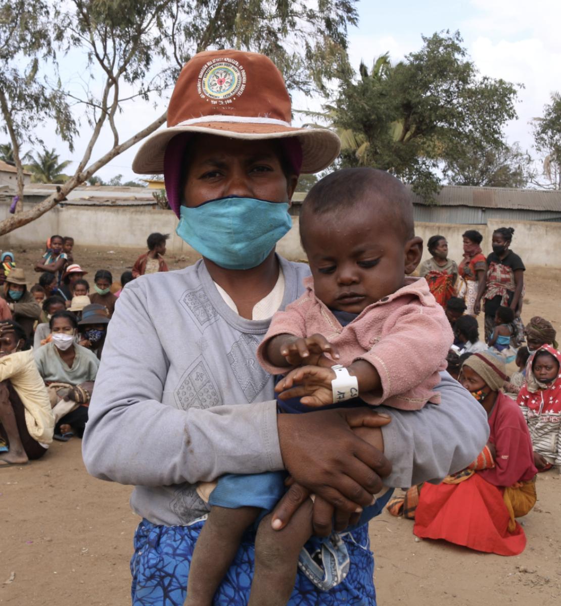 一个戴着面具和帽子的妇女怀里抱着一个婴儿,一大群人坐在她身后。