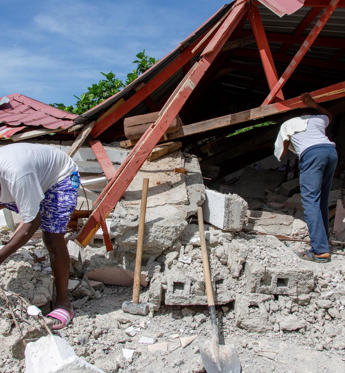 Deux hommes examinent les décombres d'un bâtiment détruit par le séisme de magnitude 7,2 qui a frappé Haïti le 24 août 2021.