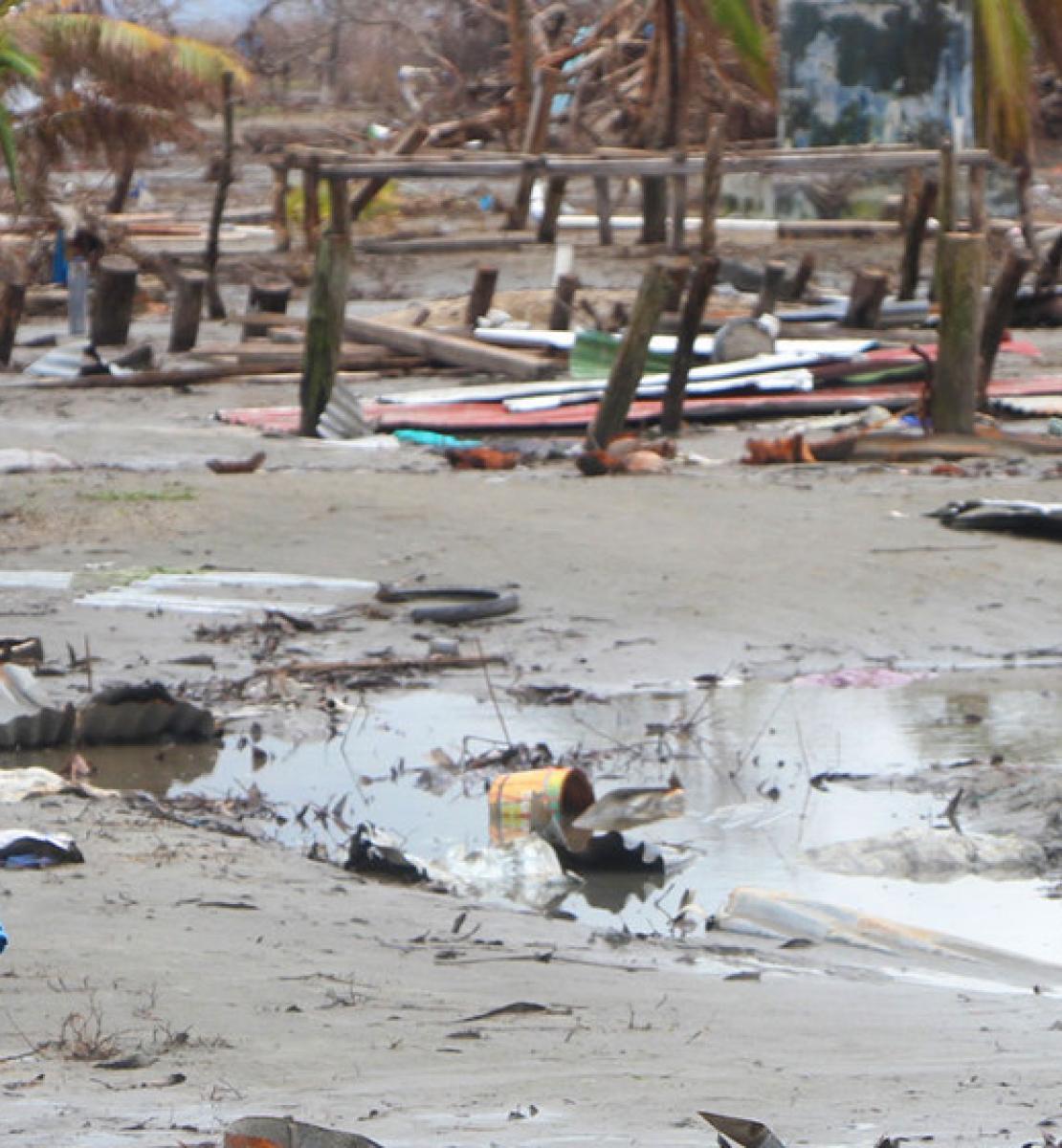 Un niño en primer plano, con un fondo de barro a sus espaldas, entre los escombros de lo que fue su hogar.