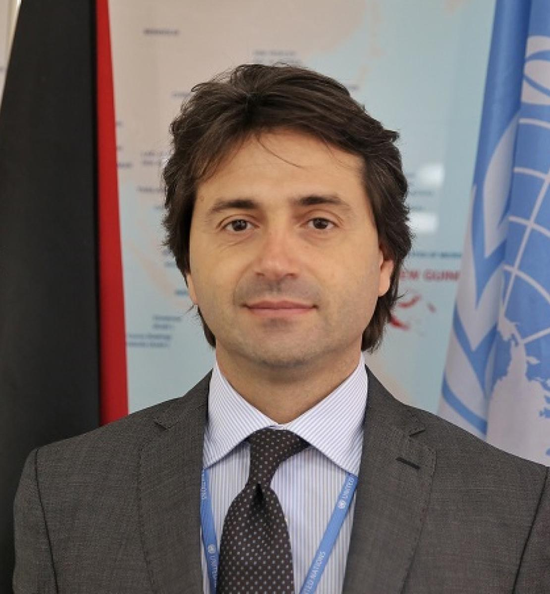 Portrait de Gianluca Rampolla del Tindaro, le nouveau Coordonnateur résident des Nations Unies au Venezuela, avec le drapeau de l'ONU en arrière-plan.