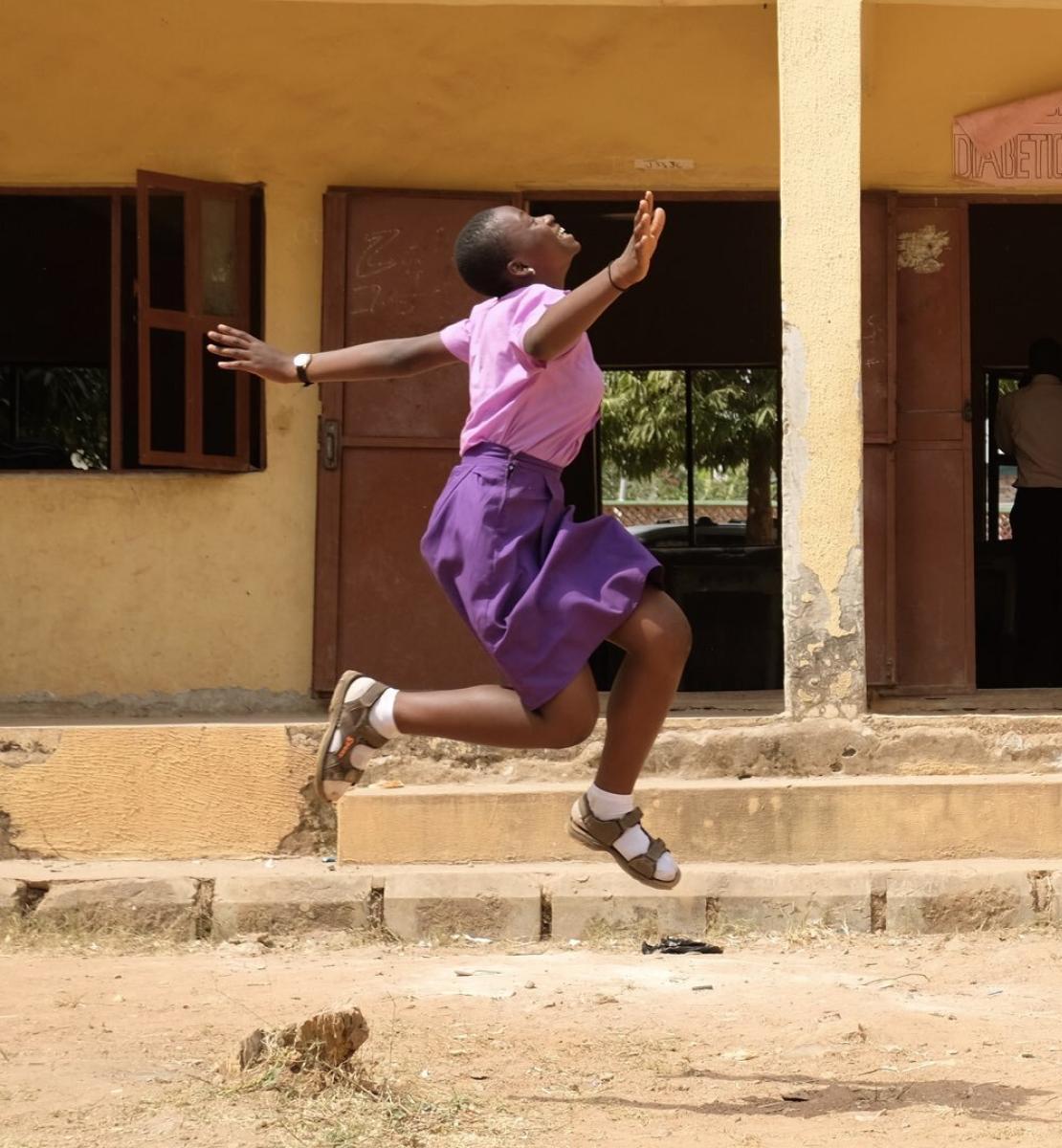 一个身穿粉色衬衫和紫色连衣裙的年轻女孩在一栋教学楼附近蹦蹦跳跳。