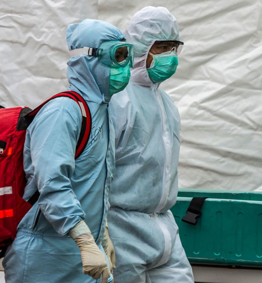 Two health care workers in full body medical gear and face masks walk with a large red backpack.