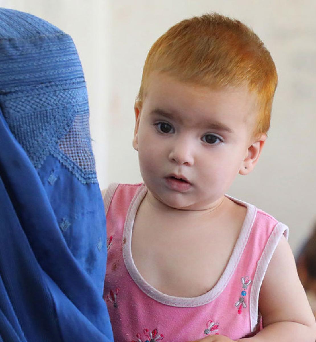 En primer plano aparece una madre con tocado y rostro mientras sostiene a su bebé, y en segundo plano se encuentra otra madre y su pequeño.