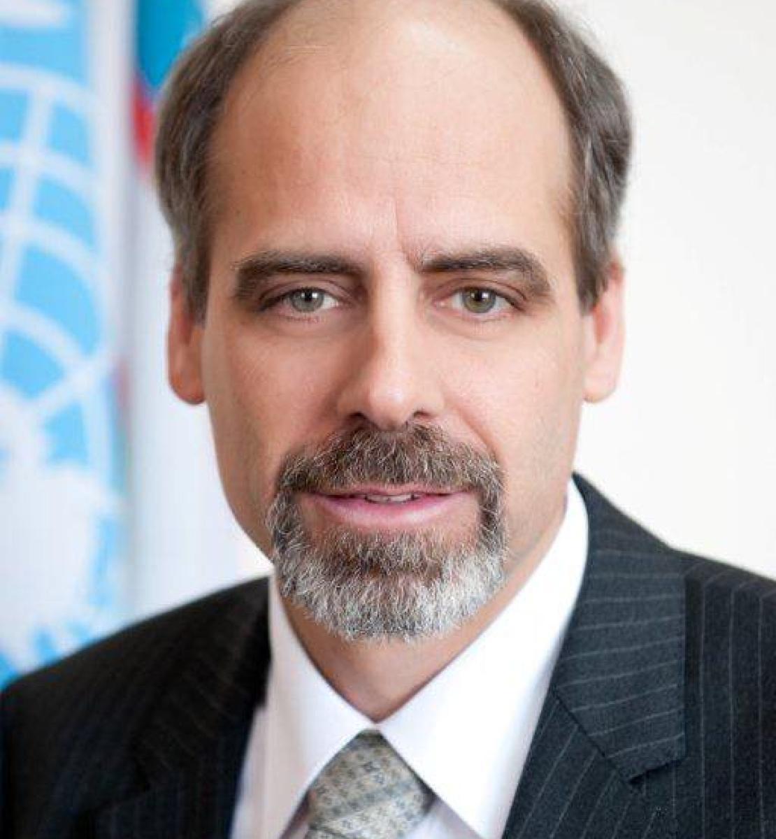 رجل ينظر مباشرة إلى الكاميرا مع علم الأمم المتحدة في الخلفية.