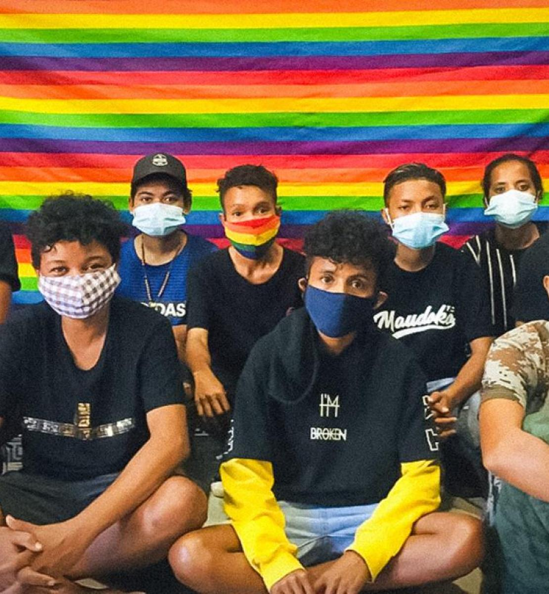 A group of young people wearing masks sit cross-legged in front of a rainbow-coloured flag.