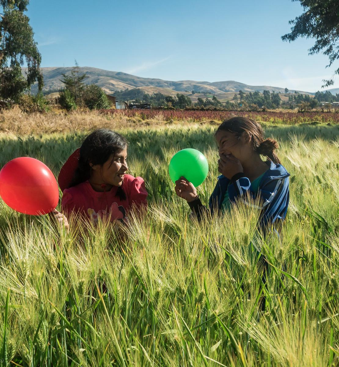 Two girls in a field play with a green and red balloon.