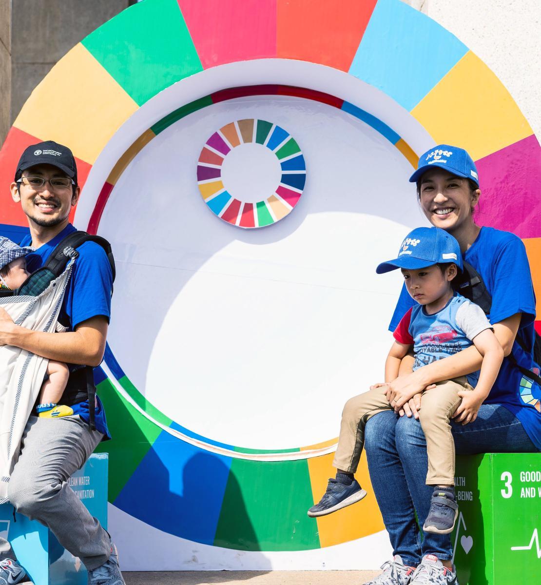 Un padre y una madre, cada uno, sostienen a un niño pequeño en el regazo, mientras sonríen alegremente a la cámara y se encuentran sentados en los extremos opuestos de una rueda con los colores de los ODS.