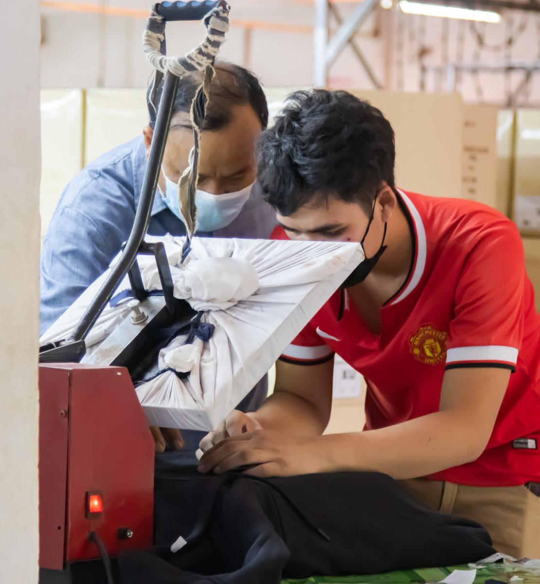 Dos hombres con mascarilla trabajan juntos en una prenda en la fábrica de ropa.