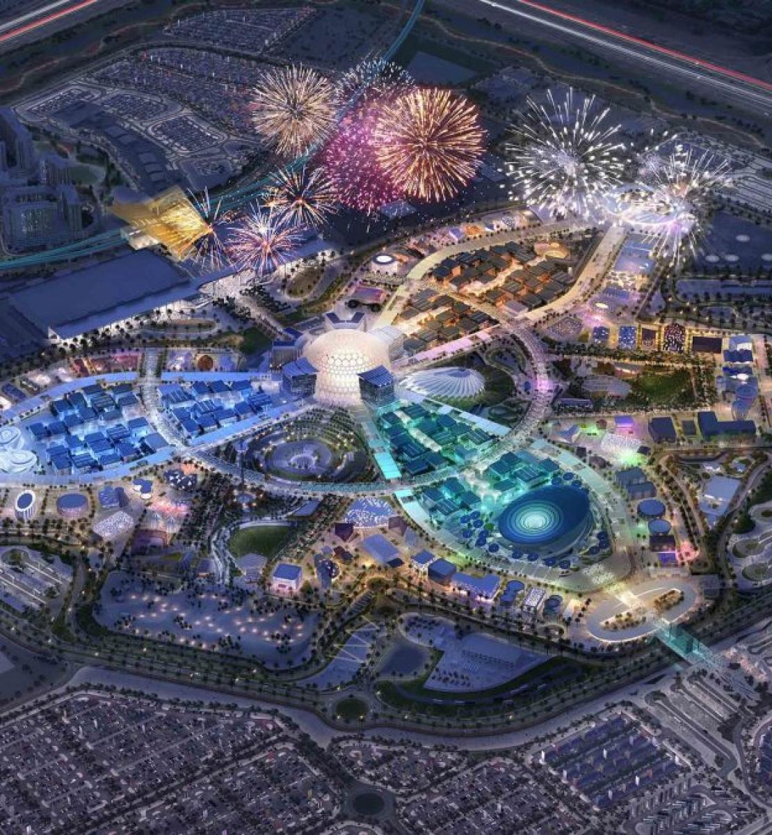 Una imagen aérea de una ciudad cuyo cielo está iluminado por fuegos artificiales.