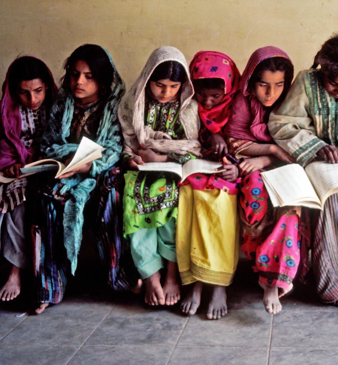 Varios niños y niñas vestidos con colores vivos miran con atención el contenido de los los libros que tiene sobre el regazo.