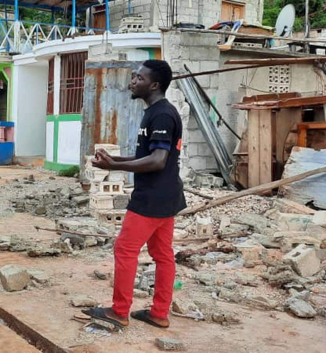 A young man in red pants speaks to a large group of volunteers and aid workers near rubble from the earthquake.
