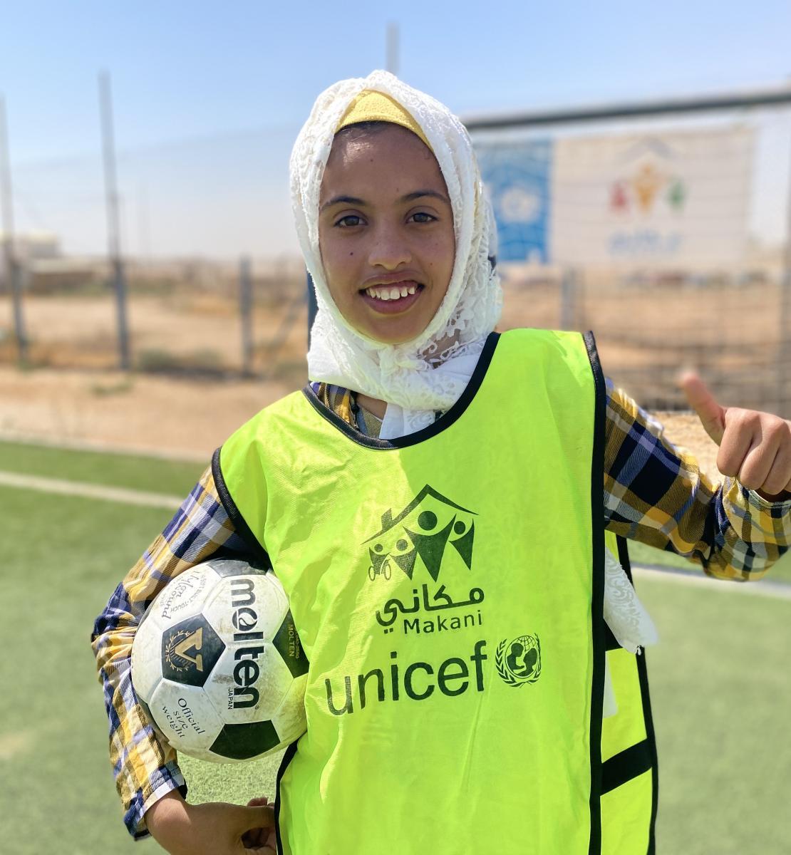 Una joven sonriente sostiene un balón de fútbol en un brazo y da a la cámara un pulgar hacia arriba con la otra mano.