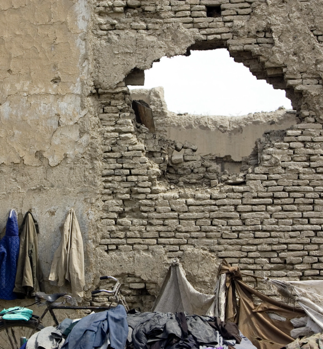 Several coats hanging outside a building with a a large hole to the right of the coats.