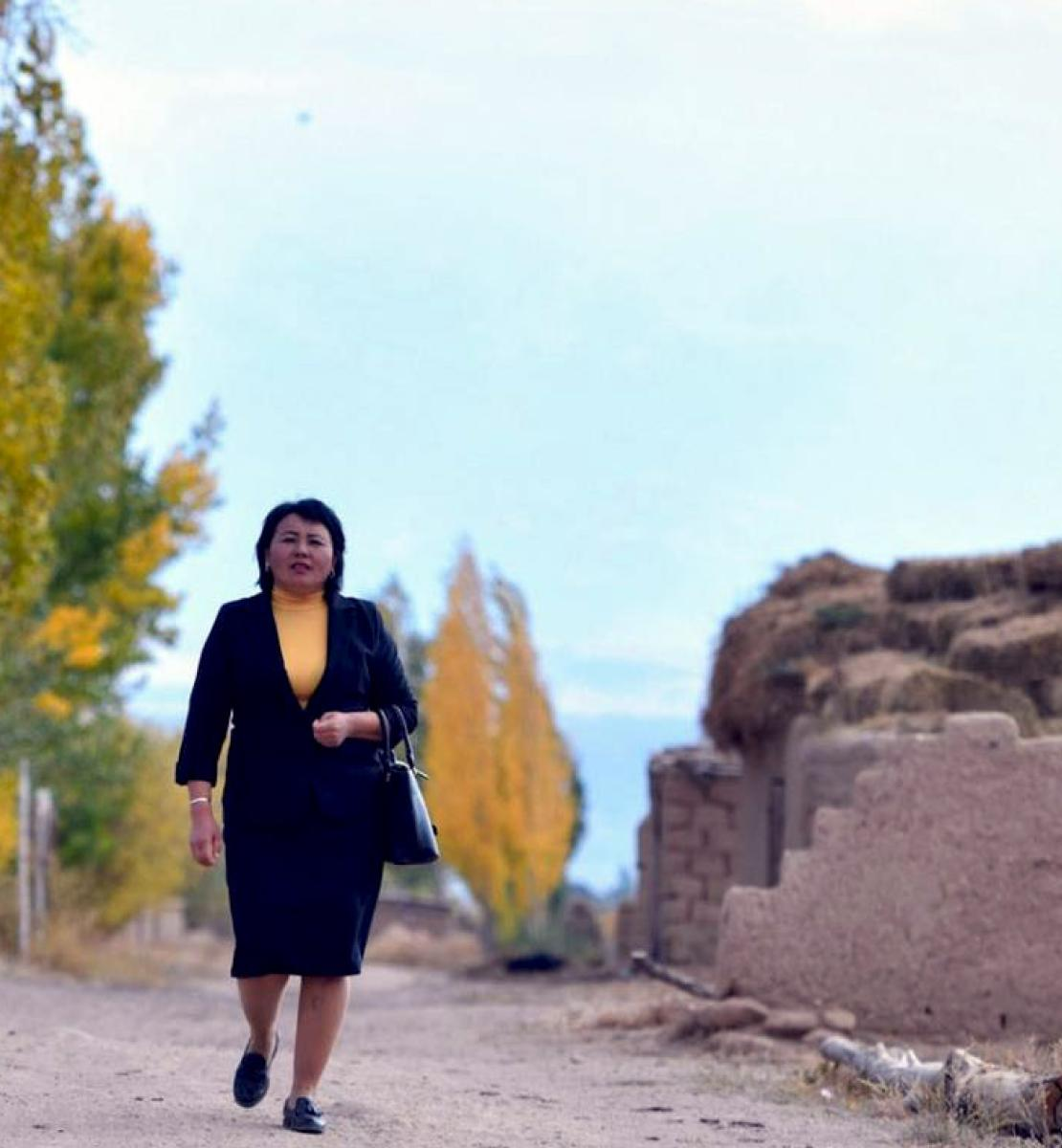 A woman in a black suit and yellow shirt walks proudly down a road towards the direction of the camera.