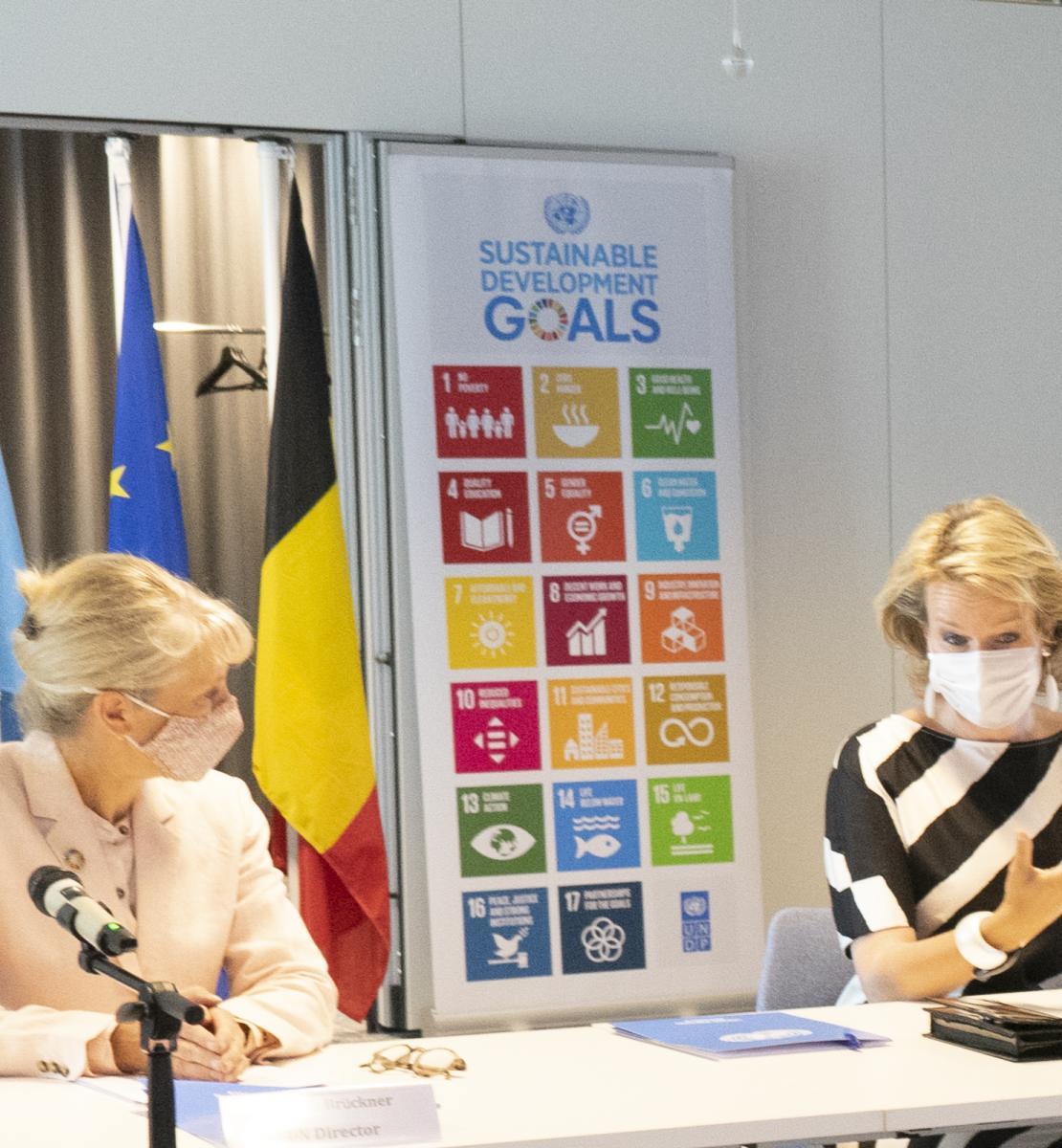 La directora de la Oficina de la ONU/PNUD en Bruselas, y Su Majestad se sientan una al lado de la otra en un escritorio, frente a los micrófonos.
