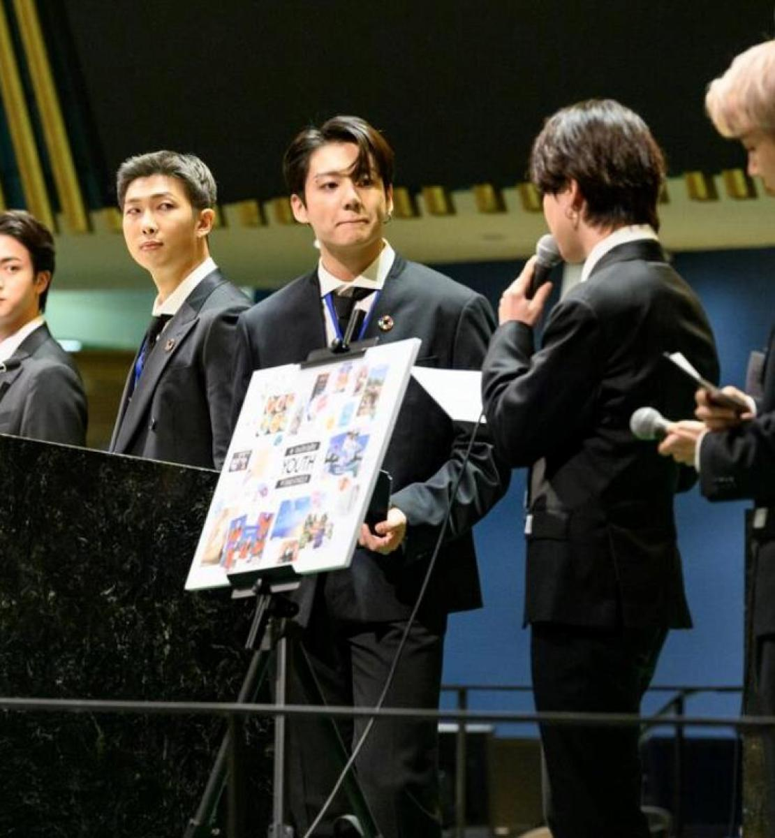 Seven members of BTS, a K-pop band, dressed in suits speak at the General Assembly.