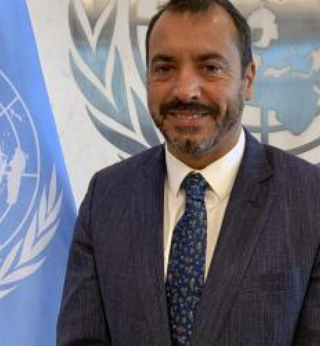رجل يرتدي بدلة وربطة عنق يبتسم للكاميرا قرب علم الأمم المتحدة الأزرق.