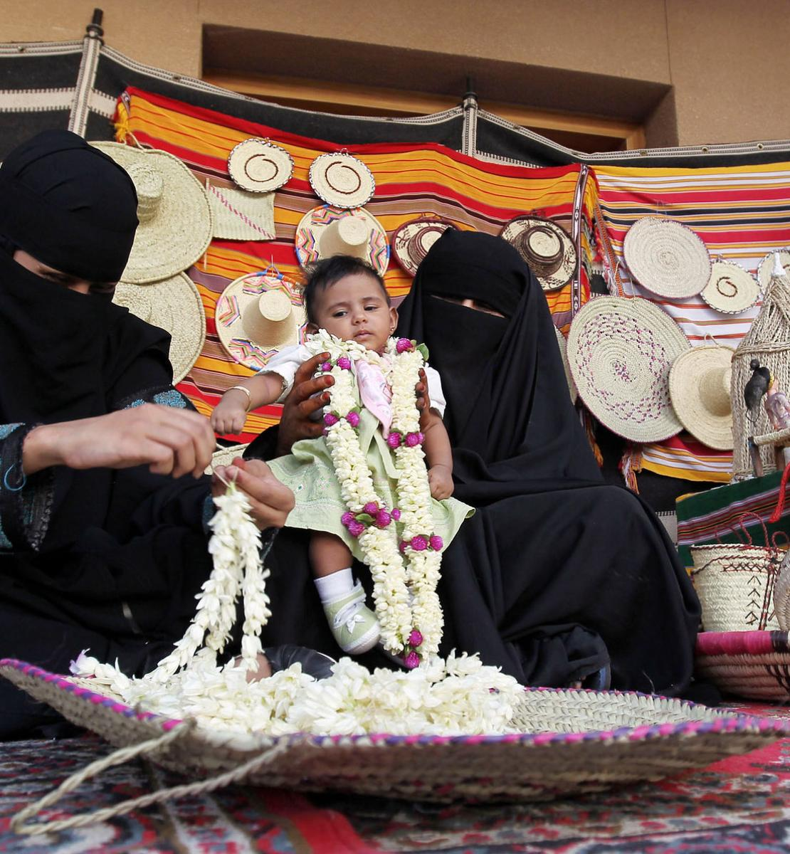 Una mujer saudí se sienta en una alfombra y enhebra flores frescas para venderlas, mientras otra mujer sentada a su lado sostiene a un bebé.