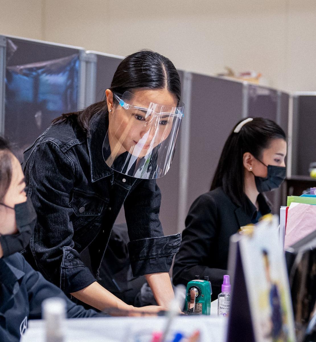 Mujeres con mascarillas y protectores faciales trabajan juntas en un escritorio de una oficina.
