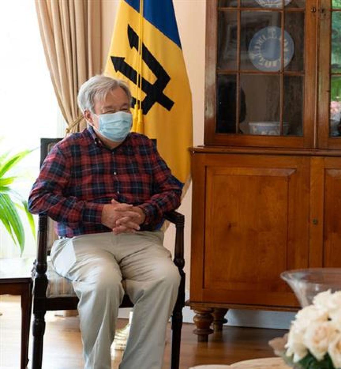 La Primer Ministro de Barbados y el Secretario General de las Naciones Unidas se sientan en sillas con las banderas de las Naciones Unidas y de Barbados detrás de ellos.