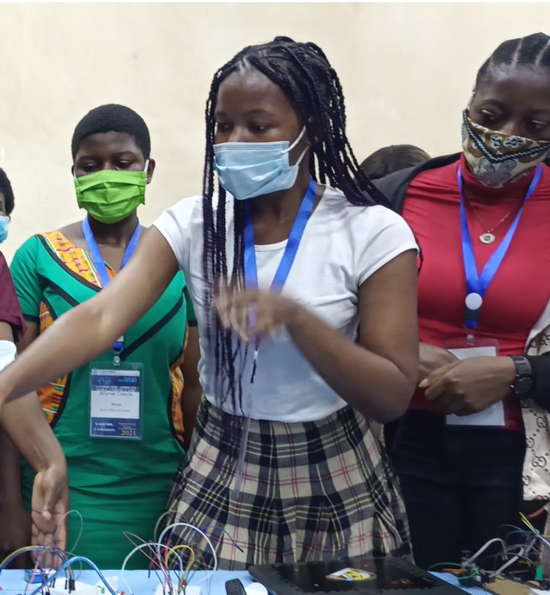 A group of young girls in masks point to computers.