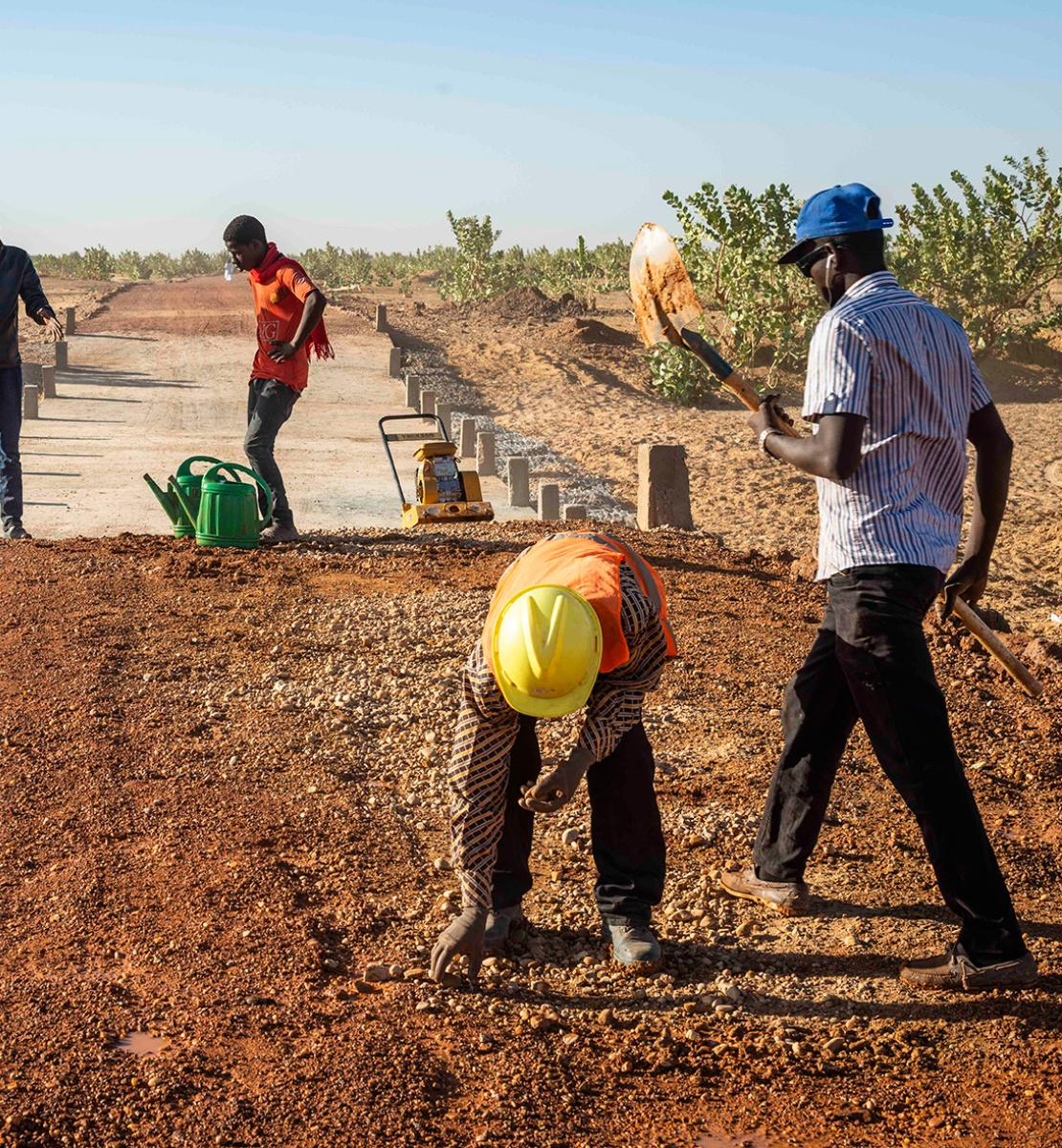 An image of four people working on a construction site in the desert.