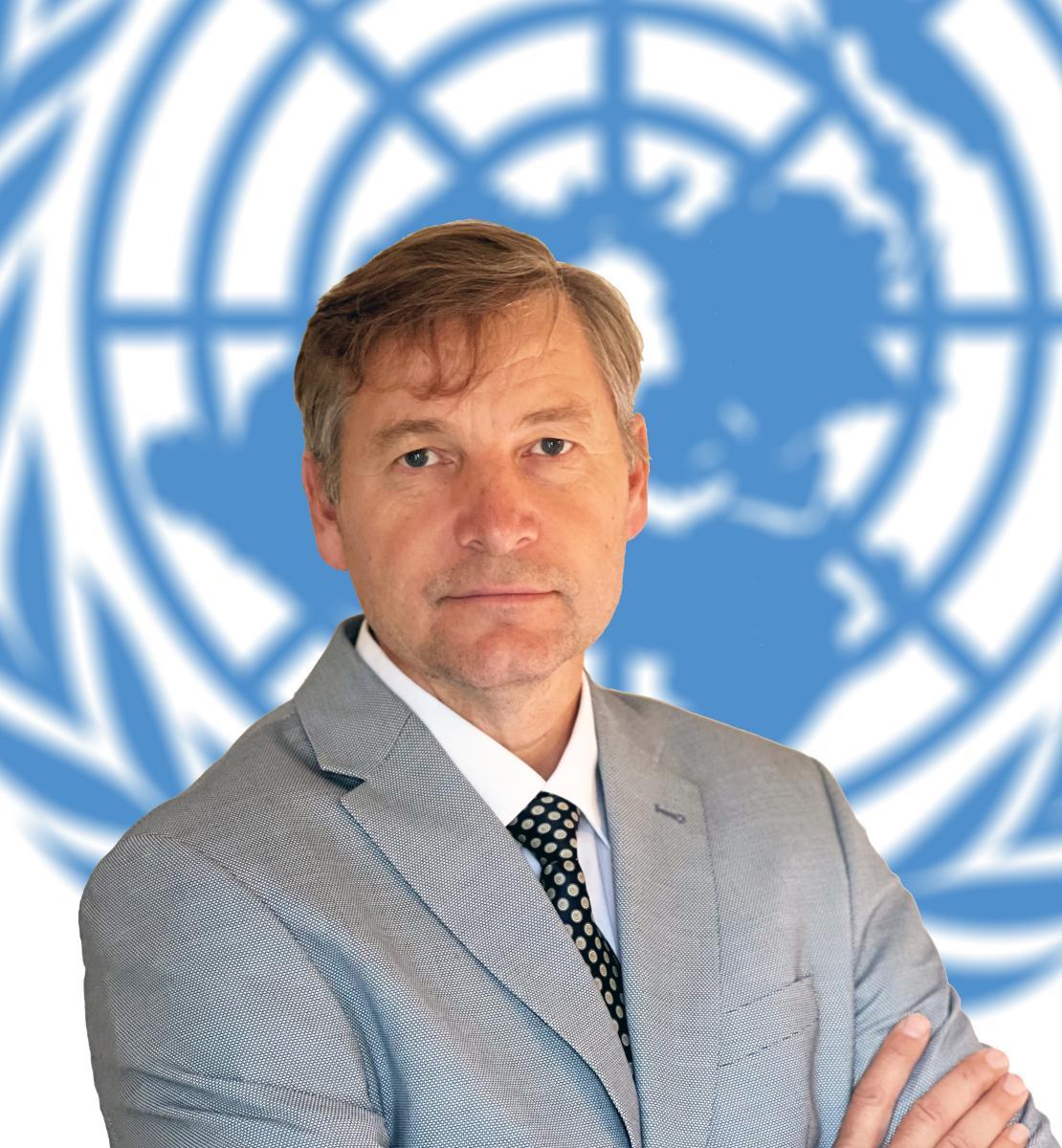 Un hombre, con un traje gris, con los brazos cruzados mira directamente a la cámara con el emblema de las Naciones Unidas como fondo.