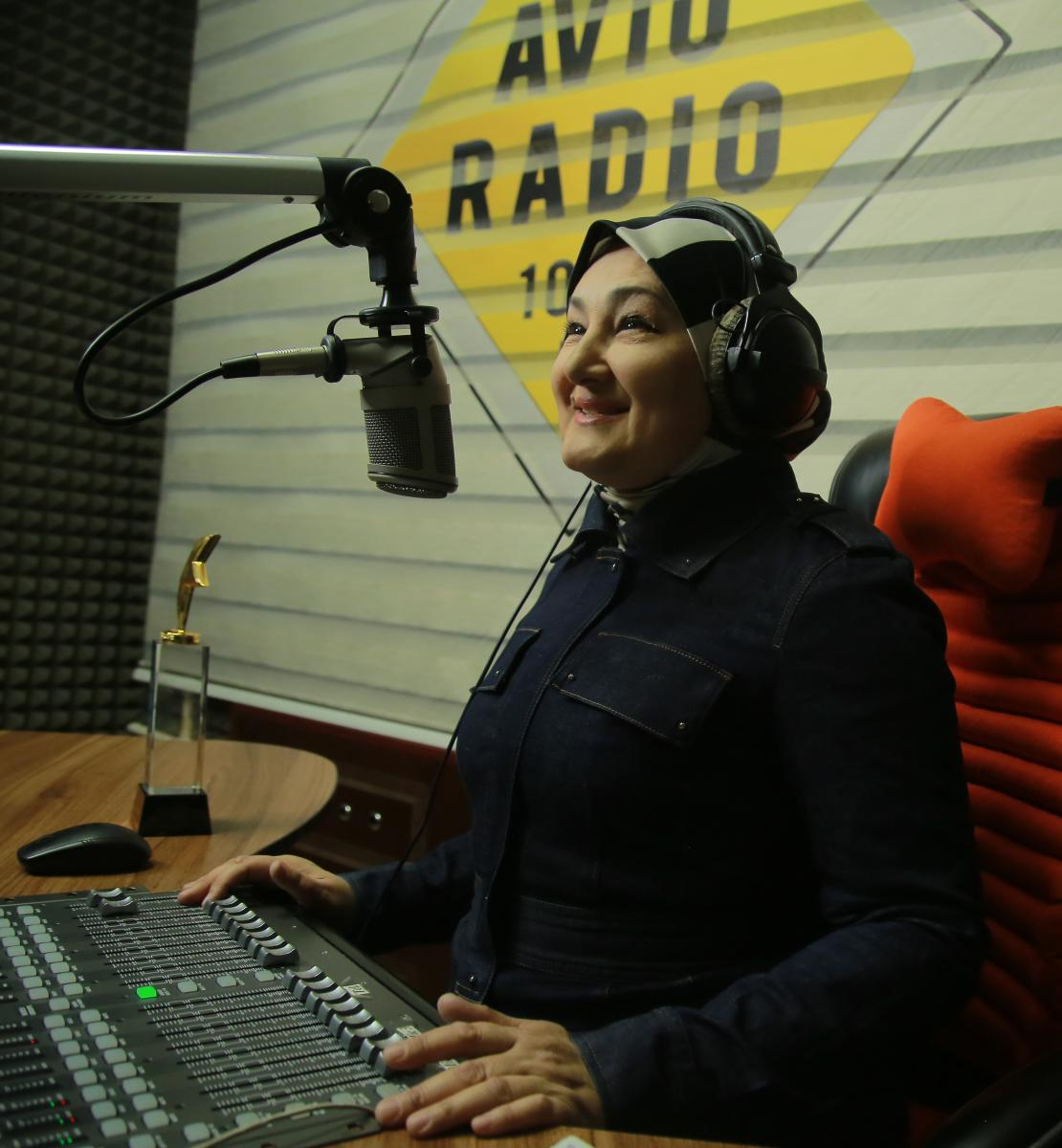 A woman dressed in black sits at a desk with a microphone and radio equipment.