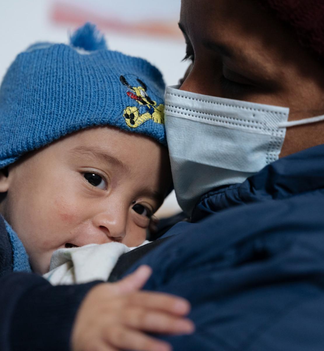 Un bebé con un gorro azul descansa sobre el hombro de su madre, quien lleva una mascarilla.