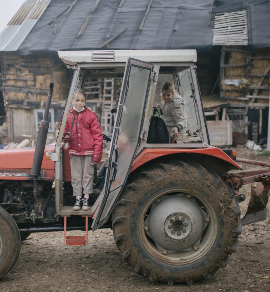 Dos chicas montan en un tractor destartalado, en una granja.