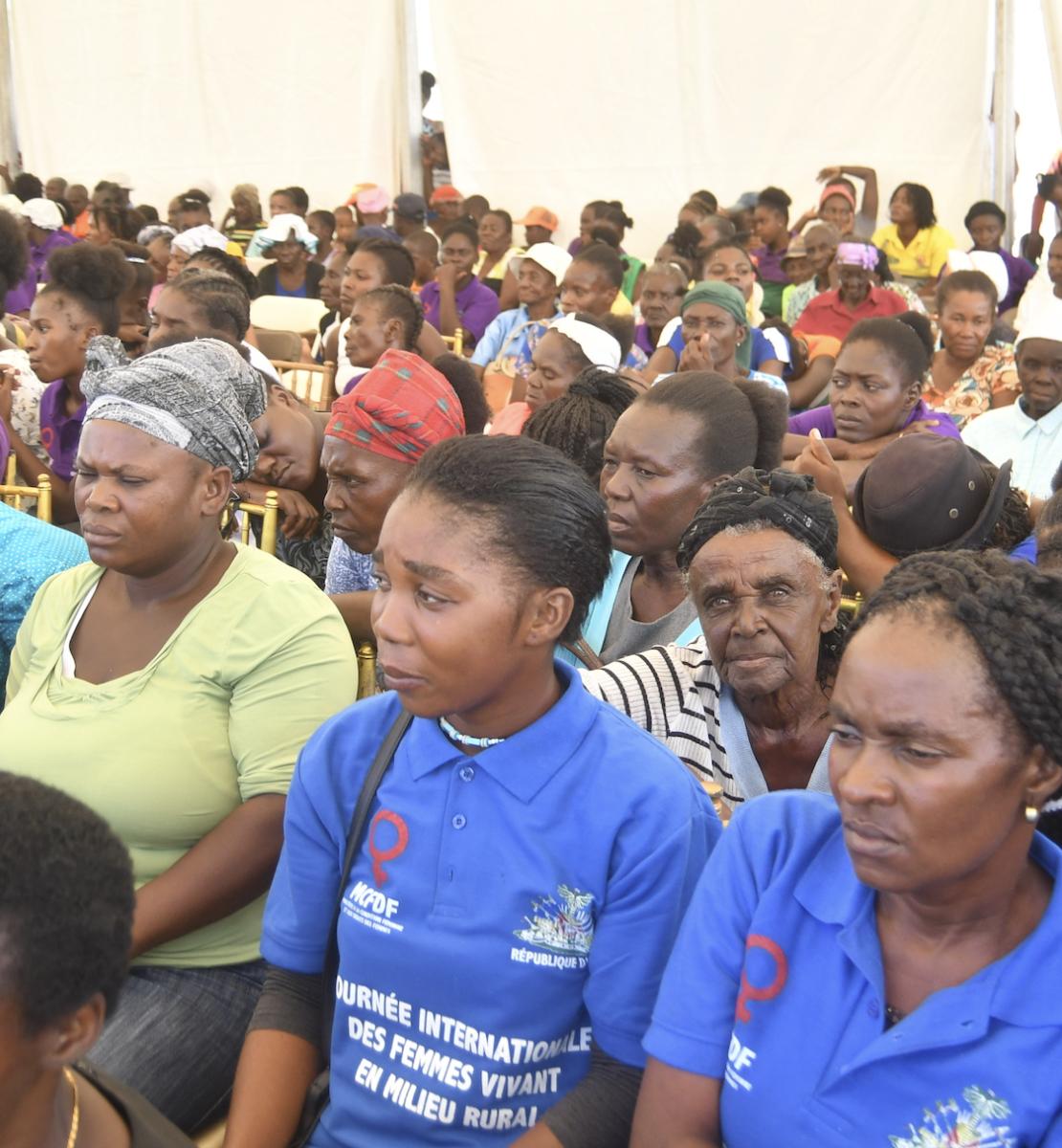 Un numeroso grupo de mujeres se sientan juntas en una gran tienda de campaña.