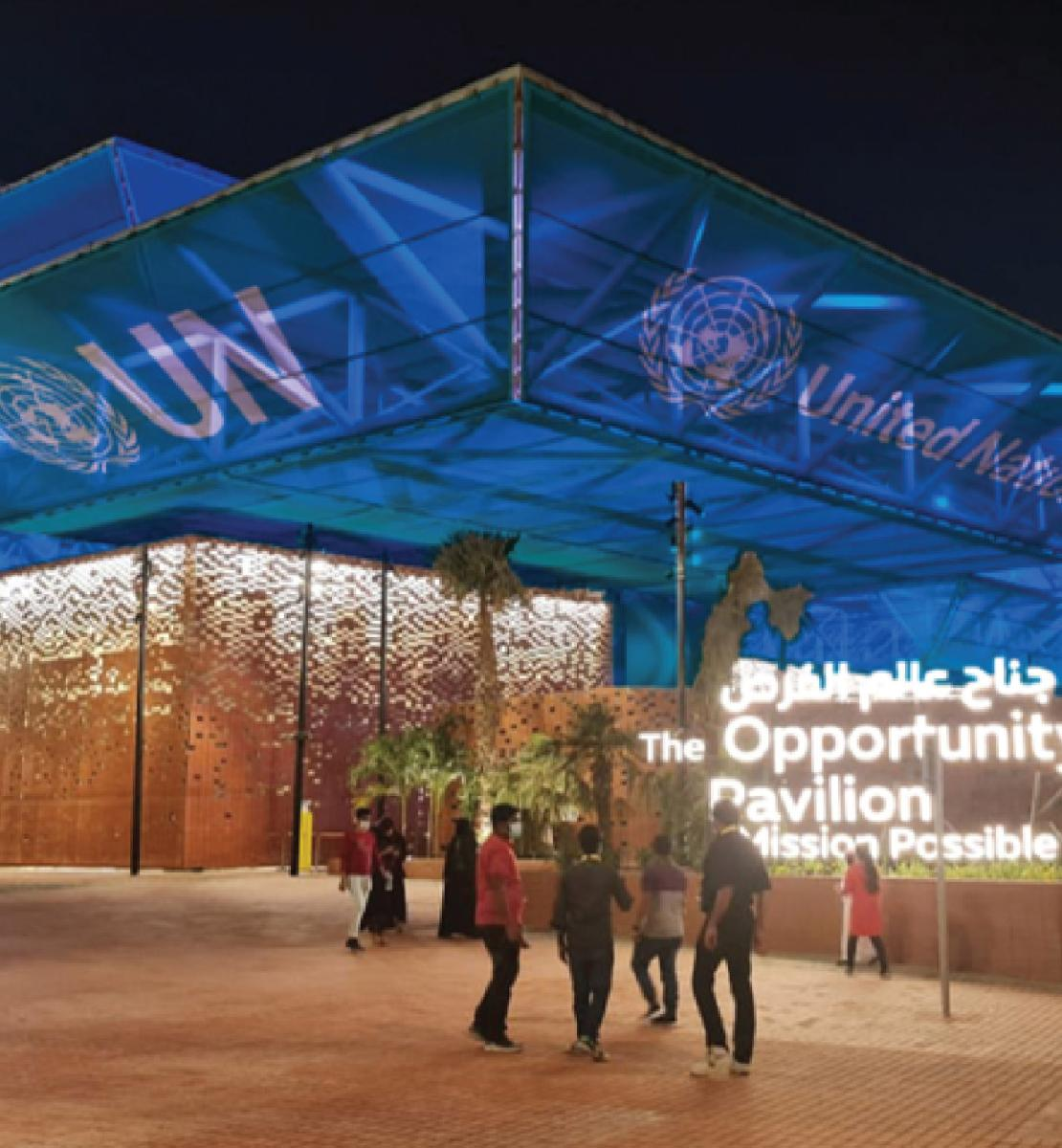 A photo of the exterior of the expo centre, showing people outside in the evening with text projected onto the building.