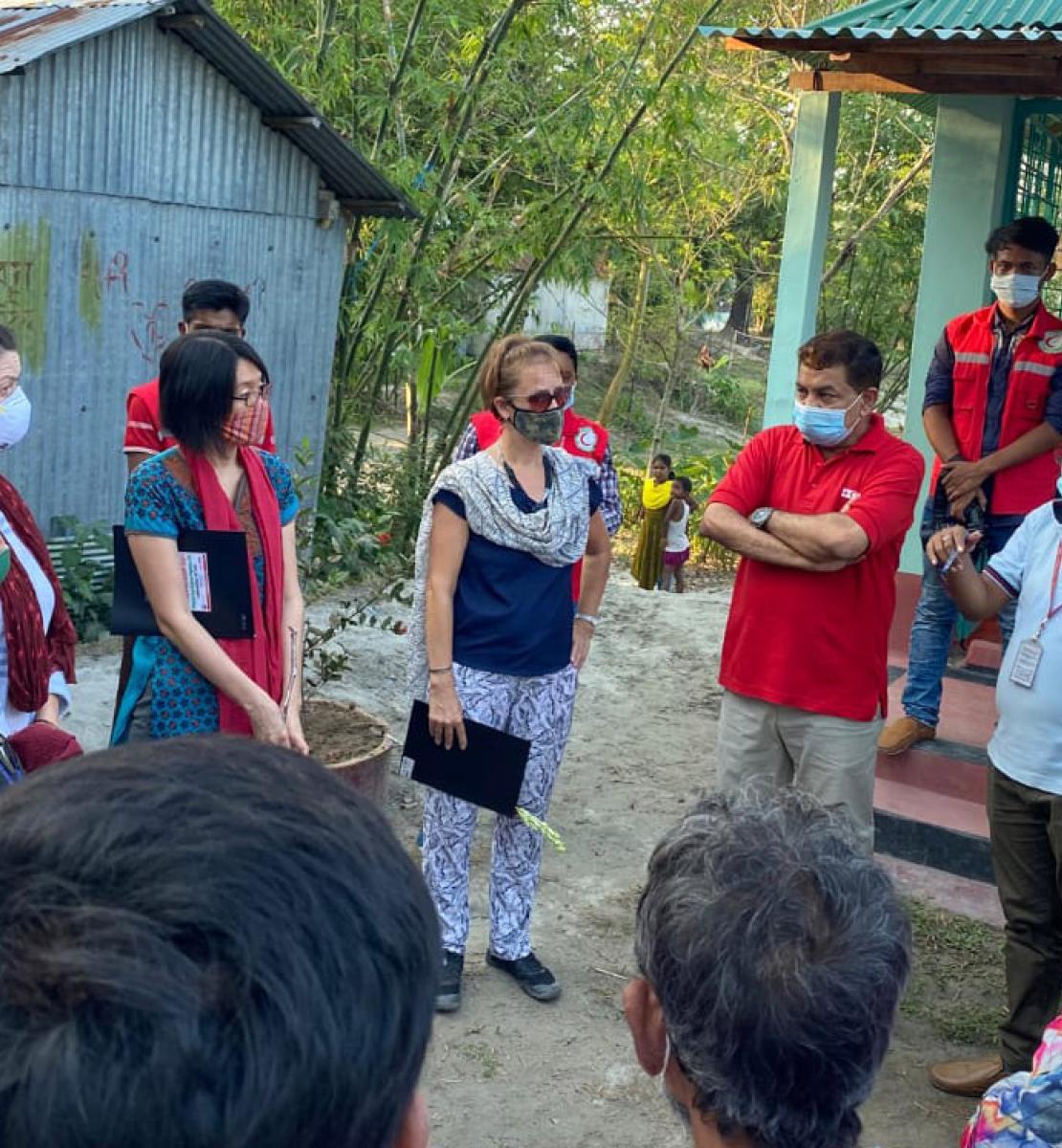 La Coordinadora Residente, Mia Seppo, se encuentra junto a un gran grupo de personas con mascarillas que se sitúan en un círculo, en un espacio al aire libre.