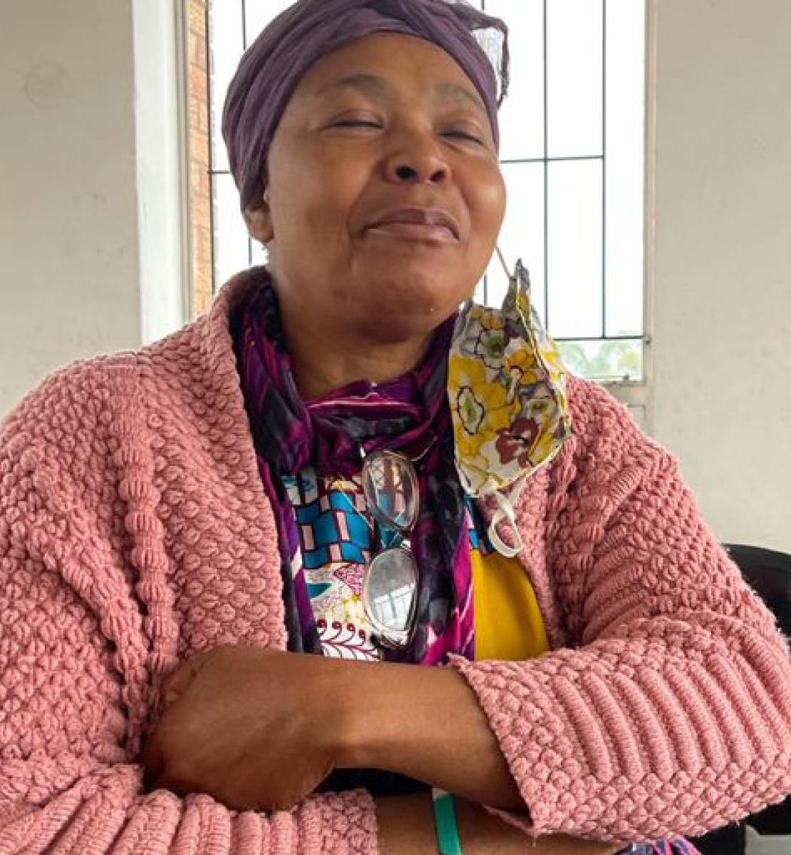 Una mujer mayor con un jersey rosa se sienta con los brazos cruzados en una habitación blanca.