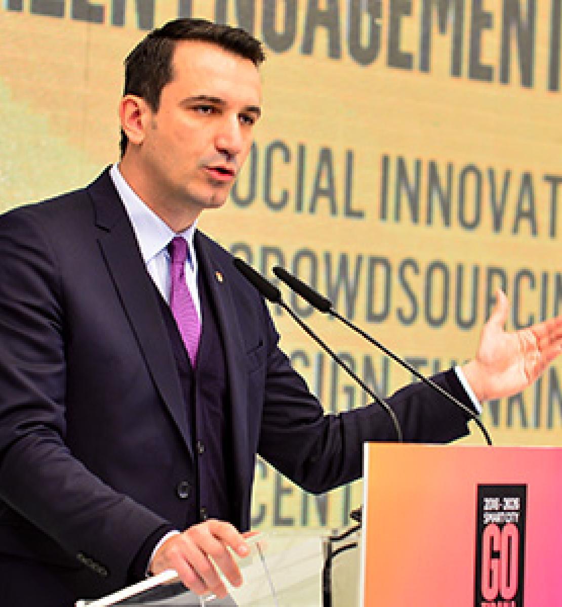 Un homme en costume cravate se tient debout derrière un pupitre et prononce un discours.