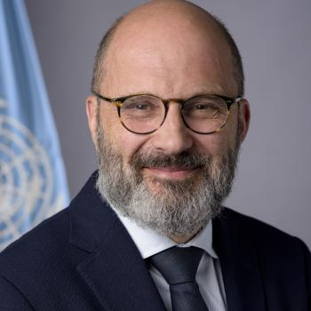 The official photo of Robert Piper shows him smiling in front of the UN flag.