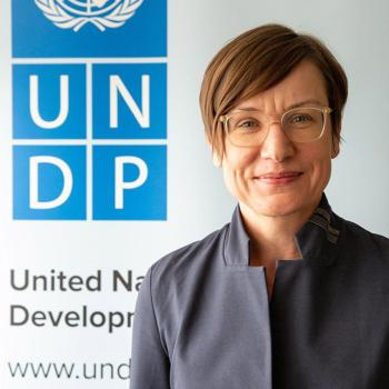 A woman with glasses stands in front of the UNDP sign.