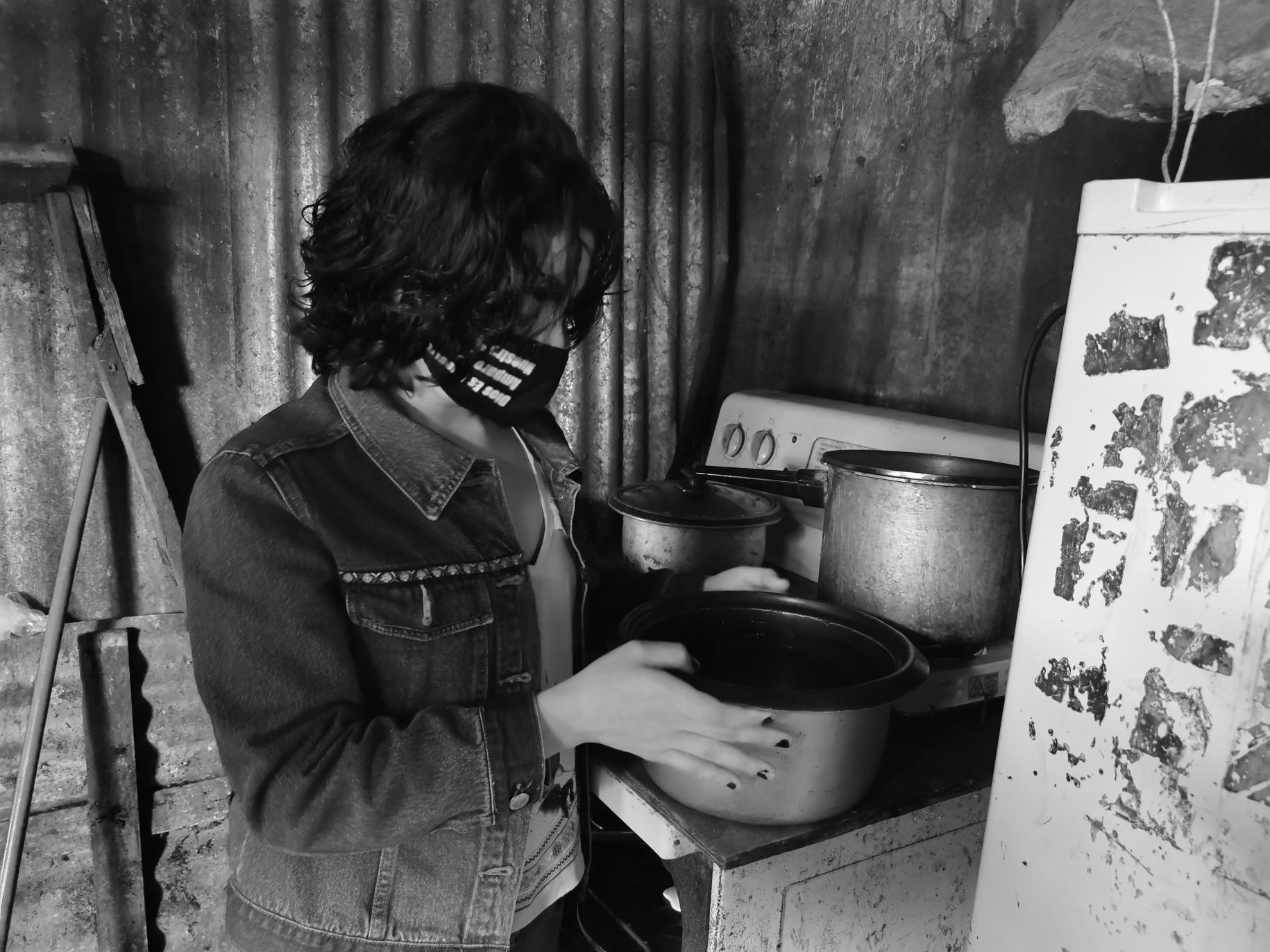 Lilith wearing a face mask sets a pot on the stove in her kitchen.
