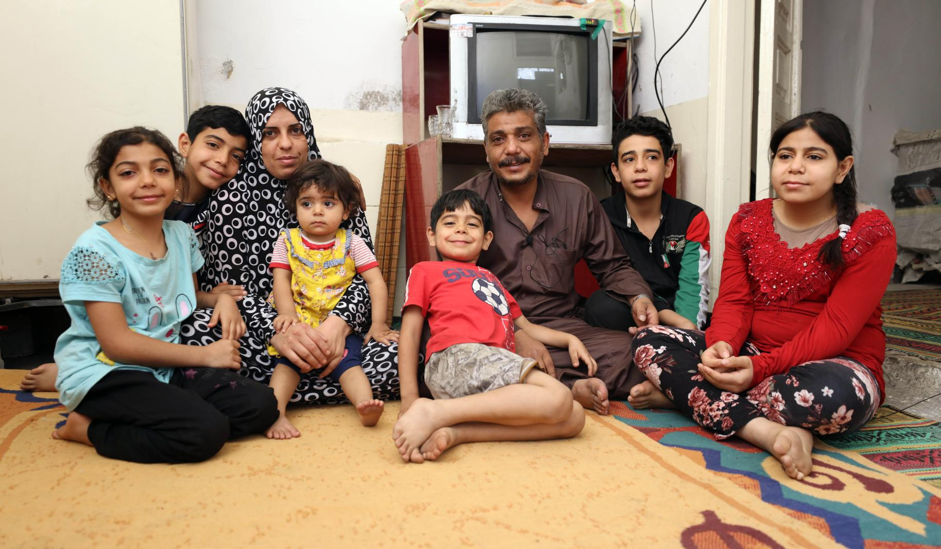 Khaled sits in their tv room on the floor with his family surrounding him.