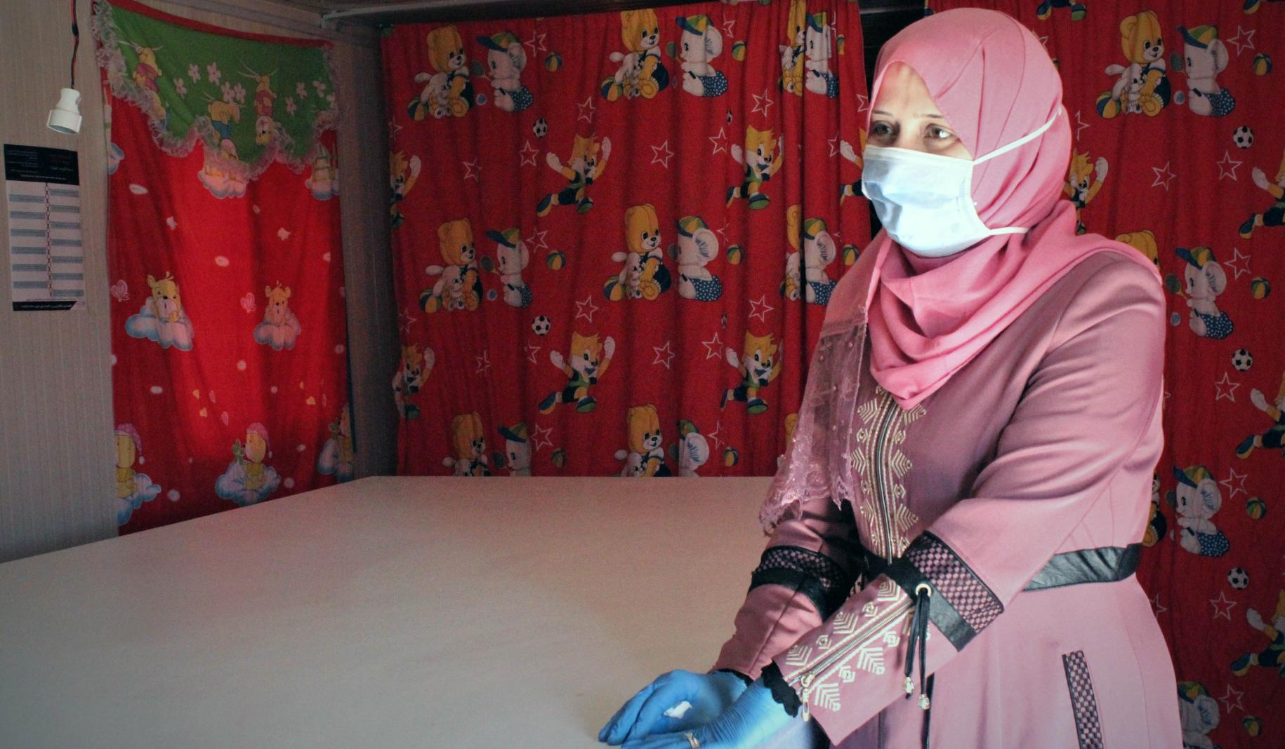 Haifa, 33, wears a face mask and gloves as she stands by a table in a room with red curtains.